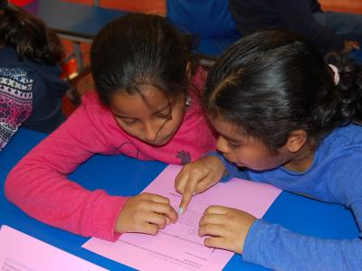 Two girls working together to read a passage.